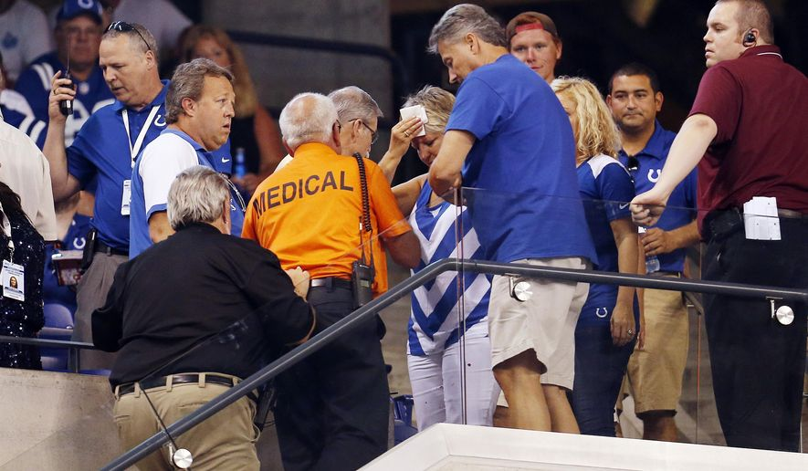 A fan is helped by emergency workers after getting injured by falling debris as the roof was opened during halftime of an NFL preseason football game between the Indianapolis Colts and the Cincinnati Bengals, Thursday, Sept. 3, 2015, in Indianapolis. (AP Photo/AJ Mast)