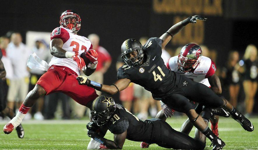 Western Kentucky running back Leon Allen (33) is tackled by Vanderbilt safety Oren Burks (20) and linebacker Zach Cunningham (41) during the first quarter of an NCAA college football game in Nashville, Tenn., Thursday, Sept. 3, 2015. (Jae S. Lee / The Tennessean via AP)