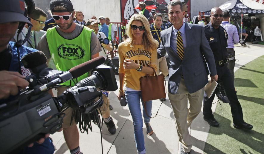 Michigan coach Jim Harbaugh and his wife, Sarah Harbaugh, arrive before for Michigan's NCAA college football game against Utah on Thursday, Sept. 3, 2015, in Salt Lake City. (AP Photo/Rick Bowmer)