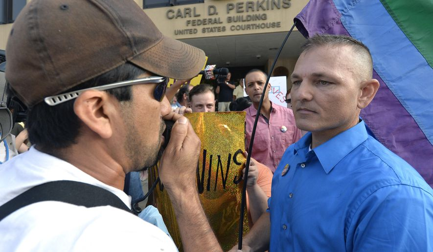 Edgar Orea, left, and Dwayne D. Beebe-Franqui argue on the steps of the Carl D. Perkins Federal Building in Ashland, Ky., Thursday, Sept. 3, 2015. Orea, a supporter of Rowan County Clerk Kim Davis, and Beebe-Franqui a supporter of same sex marriage were waiting for the arrival of Kim Davis in Federal Court. Davis and her deputy clerks have been summoned to a hearing Thursday before Judge David Bunning. Davis stopped issuing licenses to all couples in June after the U.S. Supreme Court legalized gay marriage. (AP Photo/Timothy D. Easley)