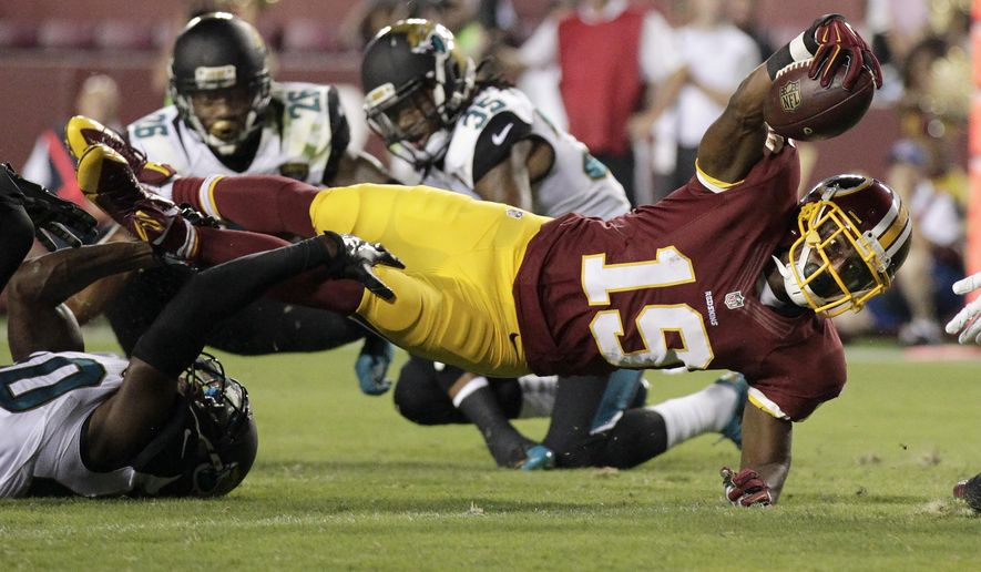 Washington Redskins wide receiver Rashad Ross (19) reaches into the end zone for a touchdown as Jacksonville Jaguars cornerback Rashaad Reynolds (40) hangs on during the first half of an NFL preseason football game in Landover, Md., Thursday, Sept. 3, 2015. (AP Photo/Mark Tenally)