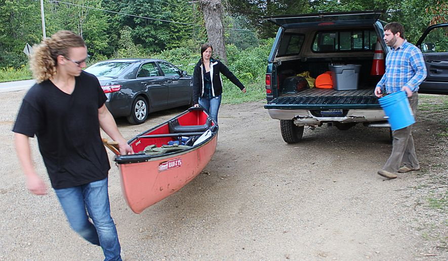 In a photo from Aug. 31, 2015, Zachary Lowes and Lauren Lucas, left, carry a canoe to a boat launch on Lake Allegan, while Justin Burchett looks on in Holland, Mich. Lowes and Lucas will be searching for and treating invasive plants in the Allegan County area as part of the Allegan Conservation District. Burchett is the district's executive director. (Caleb Whitmer/Holland Sentinel via AP)