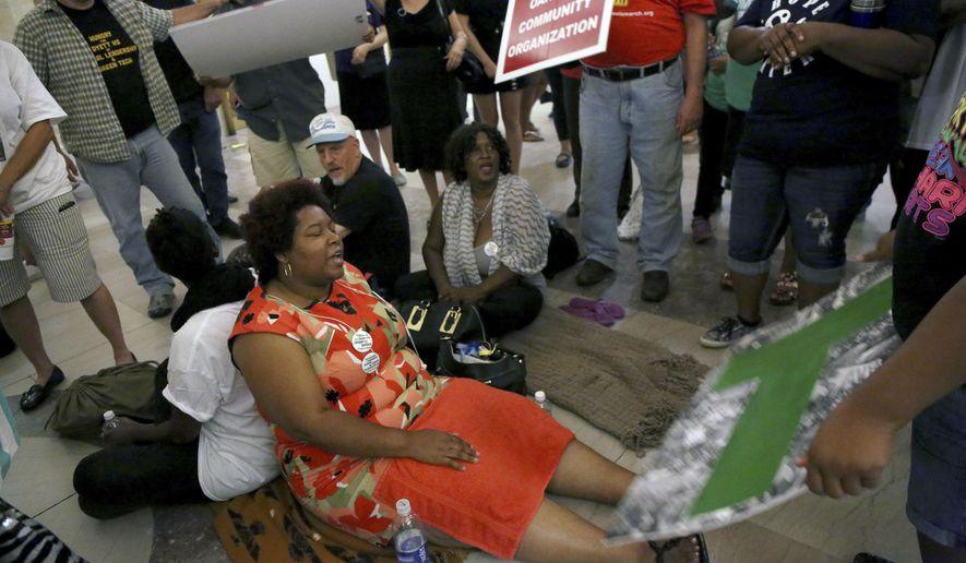 Protestors and activist sit in the lobby of City Hall Thursday, Sept. 3, 2015 in Chicago. Chicago school officials say they'll open a new arts-focused school in a neighborhood school once slated for closure. Last month activists began a hunger strike, urging their plan of a community partnership for a green technology school. (Nancy Stone/Chicago Tribune via AP) MANDATORY CREDIT CHICAGO TRIBUNE; CHICAGO SUN-TIMES OUT; DAILY HERALD OUT; NORTHWEST HERALD OUT; THE HERALD-NEWS OUT; DAILY CHRONICLE OUT; THE TIMES OF NORTHWEST INDIANA OUT; TV OUT; MAGS OUT; NO SALES