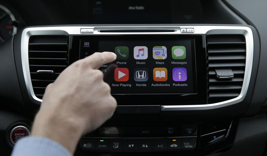 In this Thursday, Aug. 20, 2015 photo, Chris Martin from Honda North America demonstrates Apple CarPlay in Torrance, Calif. Playing deejay with voice commands will get easier for more Americans this fall as some best-selling cars get updated with software that integrates smartphones into the dashboard. (AP Photo/Jae C. Hong)
