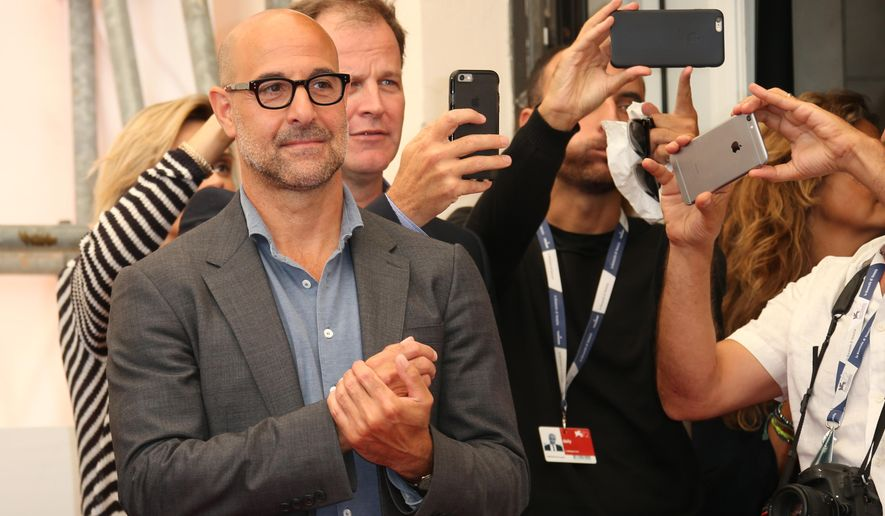 Stanley Tucci and Thomas McCarthy watch as Mark Ruffalo poses for photographers at the photo call for the film Spotlight during the 72nd edition of the Venice Film Festival in Venice, Italy, Thursday, Sept. 3, 2015. The 72nd edition of the festival runs until Sept. 12. (Photo by Joel Ryan/Invision/AP)