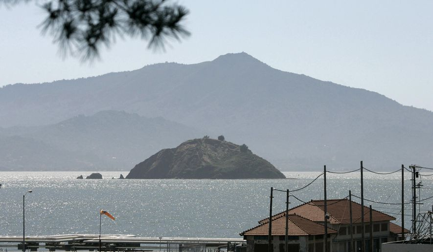 FILE - In this June 15, 2007 file photo, Red Rock Island, with Mt. Tamalpais in the background, is seen in this view taken from Point Richmond, Calif. In a city with some of the highest home prices in the county, a private island in the San Francisco Bay has had its priced slashed and is now for sale for $5 million. Red Rock, a 6-acre mass of rock, sand, vegetation and minerals, was for sale for $22 million in 2012, but then the price was slashed to $9 million without any takers. In the foreground is part of the off loading area of the Chevron oil refinery. (AP Photo/Eric Risberg, File)