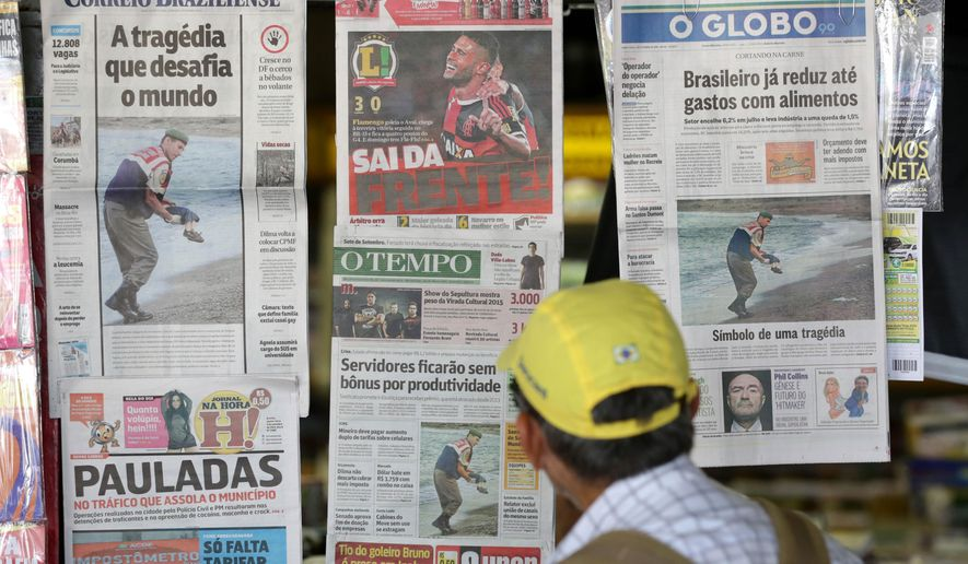 Brazilian newspaper covers show the photo of the dead 3-year-old Syrian boy on a Turkish beach, at a news stand in Brasilia, Brazil, Thursday, Sep. 3, 2015. The photo of the body washed up on the sand was splashed on the front of all major newspapers in Brazil, a nation with more homicides than any other, according to the United Nations. Still, the picture ignited despair and indignation. (AP Photo/Eraldo Peres)