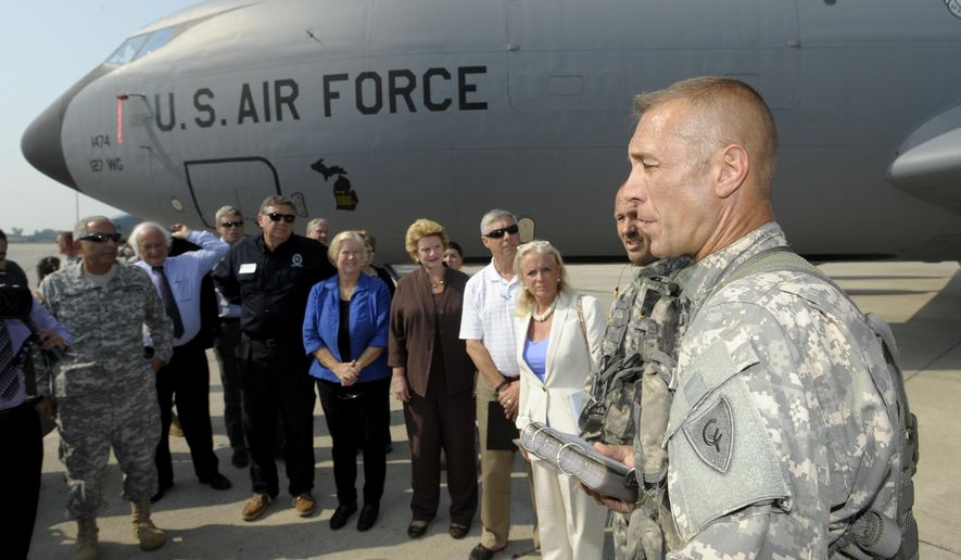 Chinook flight engineer Douglas Rawlins, right, gives a safety briefing to members of U.S. Congress and military commanders before they fly to another installation, Wednesday, Sept. 2, 2015, from suburban Detroit. Listening in front of this KC-135 Stratotanker are, from left,  Michigan's Adj. Gen. Gregory J. Vadnais, Congressmen Sandy Levin, Bill Huizenga and Dan Benishek, and Congresswomen Candice Miller and Debbie Stabenow, Congressman Fred Upton and Congresswoman Debbie Dingell. The congressional members, all from Michigan, toured Selfridge Air National Guard Base in Harrison Twp., as their first stop on a two-day-tour of major Michigan military installations.  (Todd McInturf/The Detroit News via AP)