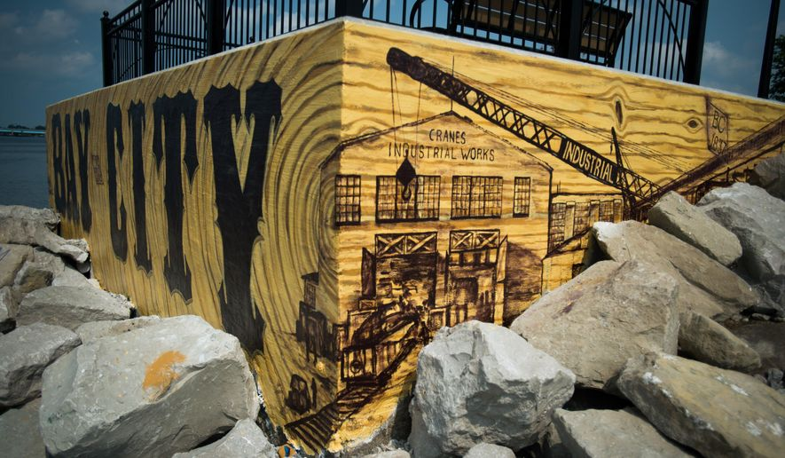 This Sept. 1, 2015 photo shows a three-sided mural painted by Bay Area Community Foundation's Youth Advisory Committee members along the Riverwalk in Bay City, Mich. The mural was painted to look like a piece of lumber on all three sides. It's designed to pay tribute to a division of the former American Hoist and Derrick Co. and Bay City's once thriving lumber industry.  (Yfat Yossifor/The Bay City Times via AP) LOCAL TELEVISION OUT; LOCAL INTERNET OUT; MANDATORY CREDIT