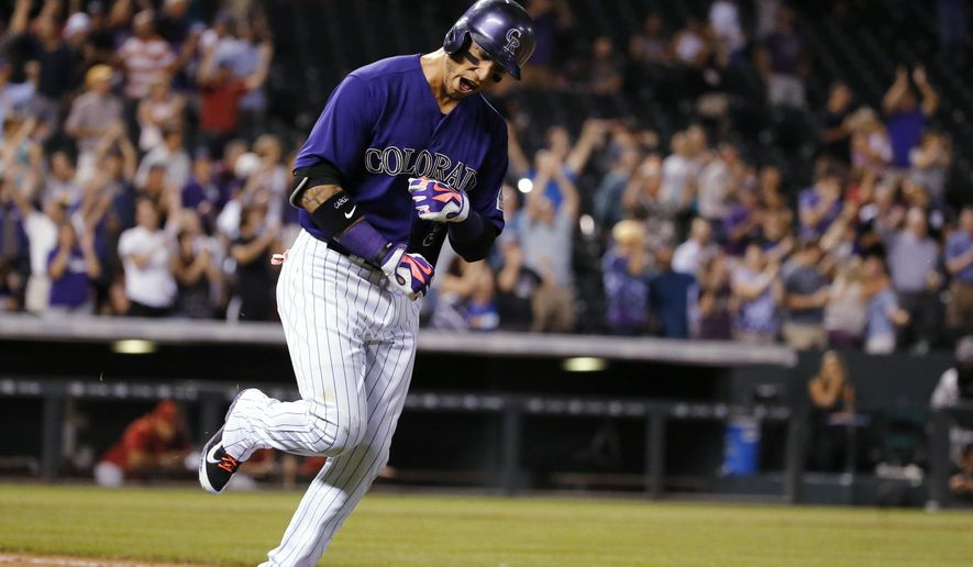 Colorado Rockies' Carlos Gonzalez reacts on his way around the bases after hitting a grand slam off Arizona Diamondbacks relief pitcher Keith Hessler during the seventh inning of a baseball game Wednesday, Sept. 2, 2015, in Denver. (AP Photo/Jack Dempsey)