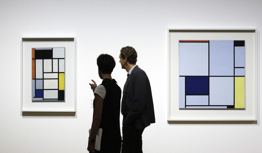 Two people pass the paintings 'Composition with Red, Black, Yellow and Gray', left, and 'Tableau I'   by  Dutch painter  Piet Mondrian during a press preview of an exhibition at the Martin-Gropius-Bau museum  in Berlin, Thursday, Sept. 3, 2015. The exhibition lasts  until Dec. 6, 2015. (AP Photo/Markus Schreiber)