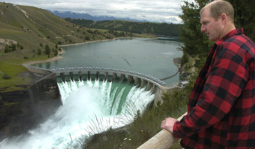 FILE - In this June 8, 2005 file photo Terry McAllister, of Bigfork, Mont., checks out the Kerr Dam, near Polson, Mont. People with business and conservation interests on the Flathead Indian Reservation are asking a judge to temporarily block federal officials from authorizing the transfer of the hydroelectric dam in northwestern Montana to the Confederated Salish and  Kootenai Tribes.  (Chris Jordan/Daily Inter Lake via AP, File) MANDATORY CREDIT