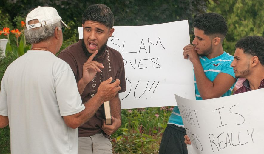 In an Aug. 18, 2015 photo, John Walker, second left, a converted Muslim, argues his point to a homeowner during a protest of the construction of a mosque on 15 Mile Road in Sterling Heights, Mich. More than 200 people gathered for a protest Saturday at the proposed site of the 20,500-square foot mosque. They said they're concerned about traffic congestion and lowered property values. (John M. Galloway/Detroit News via AP)