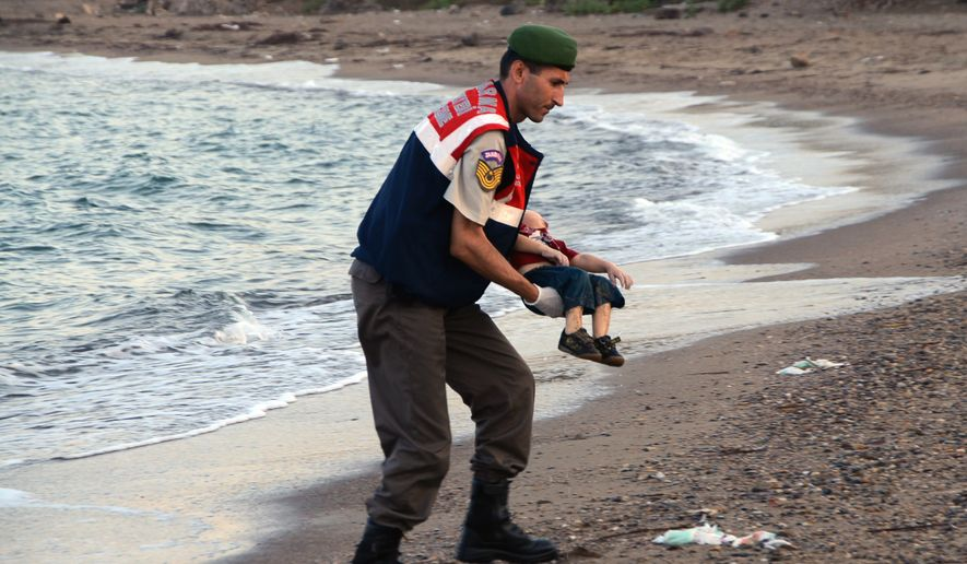 A paramilitary police officer carries the lifeless body of an unidentified migrant child, lifting it from the sea shore, near the Turkish resort of Bodrum, Turkey, early Wednesday, Sept. 2, 2015. A number of migrants are known to have died and some are still reported missing, after boats carrying them to the Greek island of Kos capsized. (AP Photo/DHA)