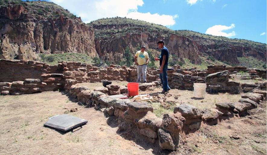 This Tuesday, July 21, 2015 photo Members of an all-Native American preservation team measure walls that are being repaired at Tyuonyi Pueblo at Bandelier National Monument near Los Alamos, N.M. The tribal youth are participating in the National Trust for Historic Preservation's HOPE project, which aims to train a new generation of preservationists. (AP Photo/Susan Montoya Bryan)