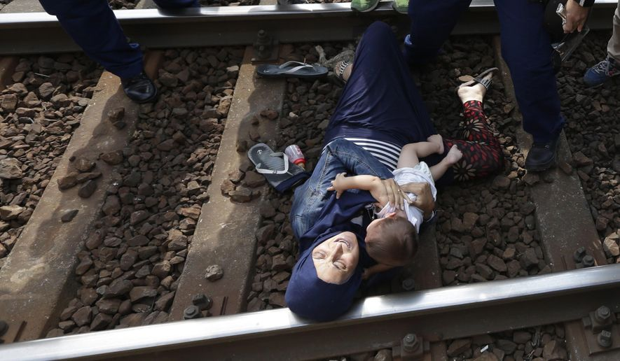 A migrant lies on the track with a baby as she is detained  in Bicske, Hungary, Thursday, Sept. 3, 2015. Over 150,000 migrants have reached Hungary this year, most coming through the southern border with Serbia. Many apply for asylum but quickly try to leave for richer EU countries. (AP Photo/Petr David Josek)