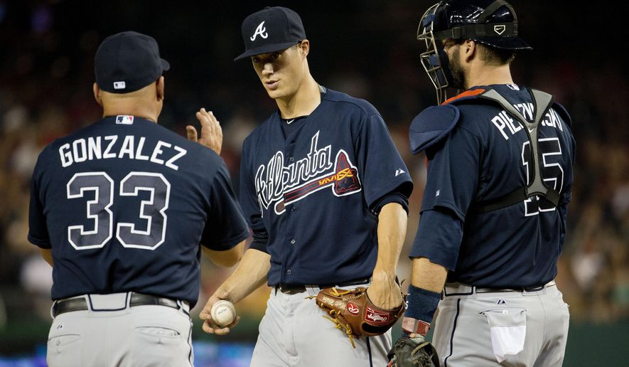 Atlanta Braves manager Fredi Gonzalez, left, takes pitcher Matt Wisler, center, out of the baseball game against the Washington National in the second inning, Thursday, Sept. 3, 2015, at Nationals Park in Washington. With them is catcher A.J. Pierzynski, right. (AP Photo/Pablo Martinez Monsivais)