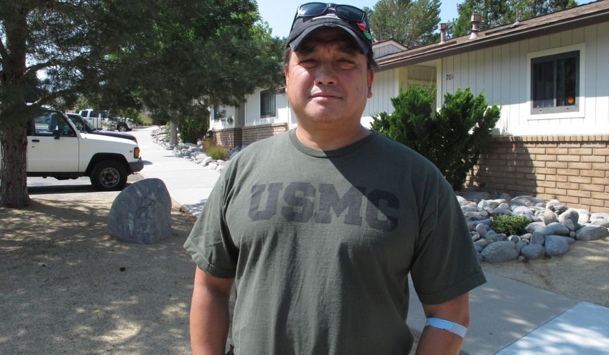 Joaquin Roces, 49, poses for a photograph on Sept. 1, 2015,  in front of his home on the north edge of Reno, Nev.,  where he's threatened with eviction after losing his job of 5 years with the Reno Housing Authority. The disabled U.S. military veteran has filed a lawsuit in U.S. District Court in Reno accusing the authority of violating federal labor laws and firing him in retaliation for complaining about unpaid wages. (AP Photo/Scott Sonner)