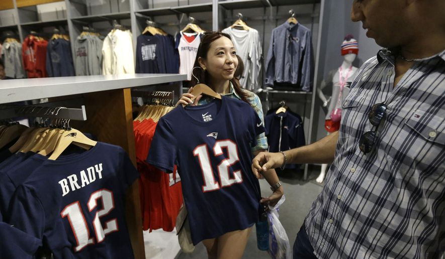 New England Patriots fans Doris Pun Chong, left, and her husband Philippe Dudley, both of Panama City, Panama, shop for a Tom Brady jersey at the Patriots ProShop at Gillette Stadium before an NFL preseason football game between the Patriots and the New York Giants, Thursday, Sept. 3, 2015, in Foxborough, Mass. Federal Judge Richard M. Berman overturned NFL Commissioner Roger Goodell's four-game suspension of New England quarterback Tom Brady Friday morning. The league said it will appeal the ruling. (AP Photo/Steven Senne)