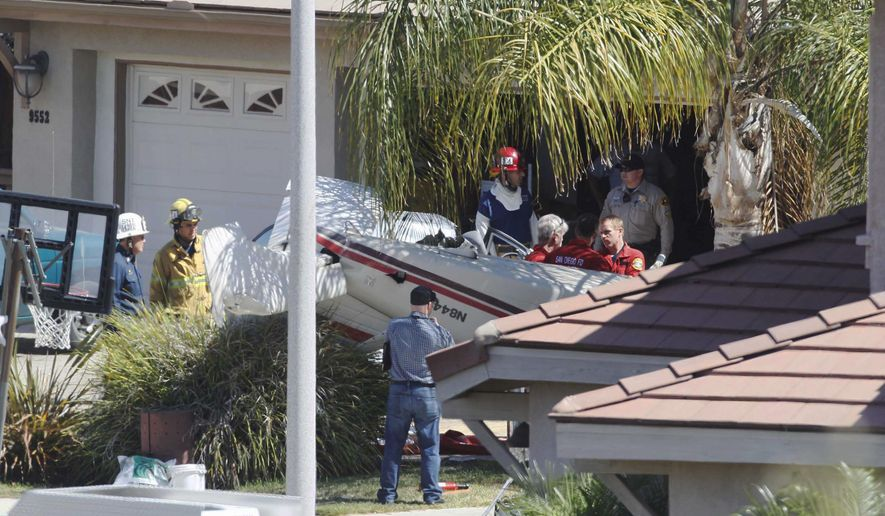 Heartland Fire units work at the scene of a small plane crash on Corte de La Donna in Santee, Calif., Thursday, Sept. 3, 2015. Authorities say one person was killed and another was critically injured when the small plane crashed about a mile from Gillespie Field airport and ended up in the driveway of a home. (John Gibbins/UT San Diego via AP)
