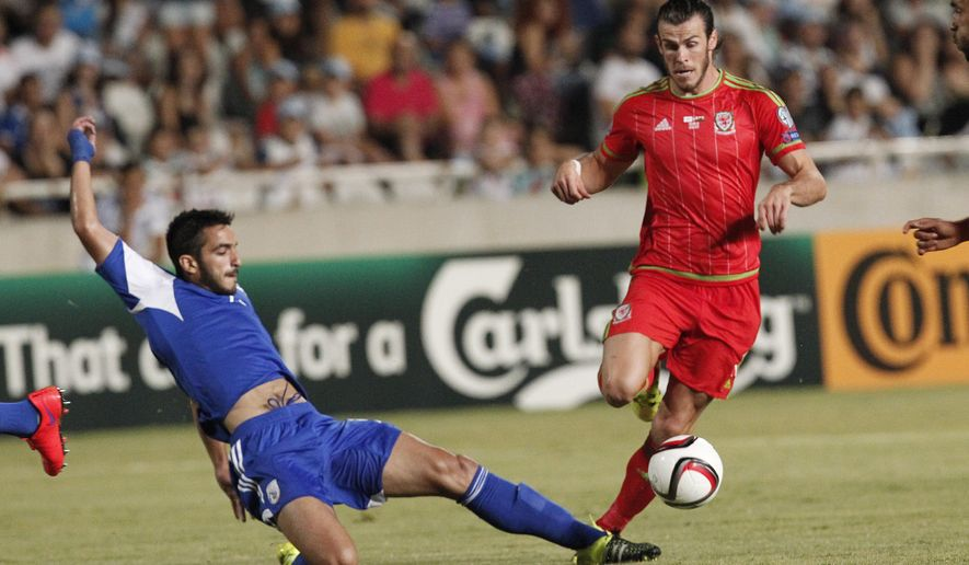 Cyprus' Kosta Laifis, left, challenges for the ball with Wales' Gareth Bale, during the Euro 2016 qualifying Group B match between Cyprus and Wales, at GSP stadium, in Nicosia, Cyprus, Thursday, Sept. 3, 2015. (AP Photo/Petros Karadjias)