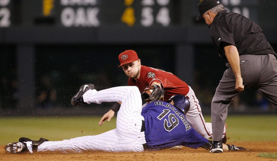 Arizona Diamondbacks shortstop Chris Owings misses the tag on Colorado Rockies' Charlie Blackmon, who doubled during the second inning of a baseball game Wednesday, Sept. 2, 2015, in Denver. (AP Photo/Jack Dempsey)