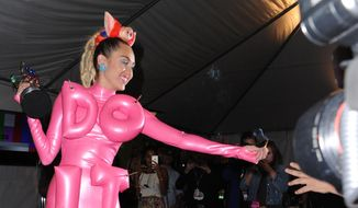 Miley Cyrus passes a lit marijuana joint to a photographer in the press room at the MTV Video Music Awards in Los Angeles in this Aug. 30, 2015, file photo. (Photo by Richard Shotwell/Invision/AP, File)