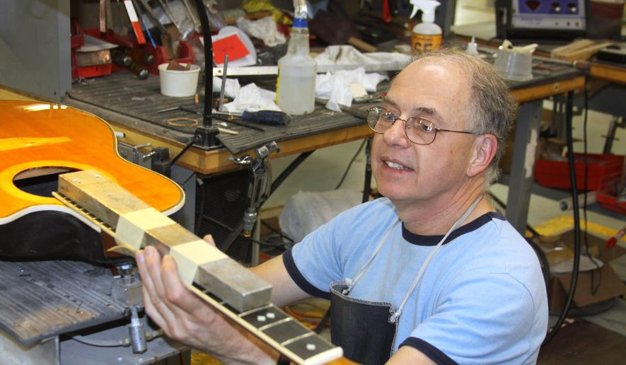 In this Monday, Aug. 31, 2015 photo, Ovation Guitars employee Mike DeNoi reattaches the neck of a customer's guitar at the factory in New Hartford, Conn. The factory that produced Ovation guitars for nearly a half century before closing last year will be making the renown instruments once again, thanks to the efforts of a factory employee who maintained the factory on his own in hopes a new buyer would revive it. (AP Photo/Kathryn Boughton)