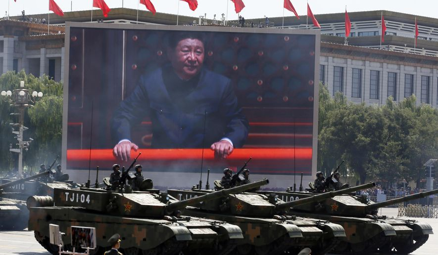 Chinese President Xi Jinping is displayed on a screen as Type 99A2 Chinese battle tanks take part in a parade commemorating the 70th anniversary of Japan's surrender during World War II held in front of Tiananmen Gate in Beijing, Thursday, Sept. 3, 2015. (AP Photo/Ng Han Guan)