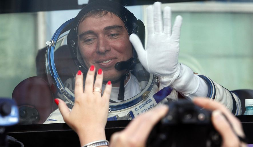 Russian cosmonaut Sergei Volkov, member of the main crew of the expedition to the International Space Station (ISS), waves to his relatives from a bus prior the launch of Soyuz-FG rocket at the Russian leased Baikonur cosmodrome, Kazakhstan, Wednesday, Sept. 2, 2015.  (AP Photo/Dmitry Lovetsky, Pool)