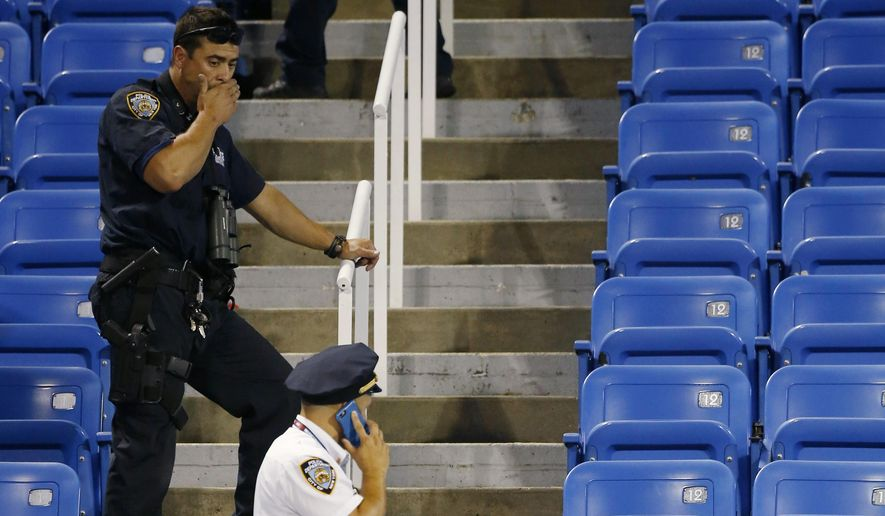 Police officers investigate the southwest corner of Louis Armstrong Stadium after a drone flew over the court, buzzing the players during a match between Flavia Pennetta, of Italy, and Monica Niculescu, of Romania, during the second round of the U.S. Open tennis tournament in New York, Thursday, Sept. 3, 2015.  The drone crashed into the seats and can be seen to the right of the police officer on his phone. (AP Photo/Kathy Willens)