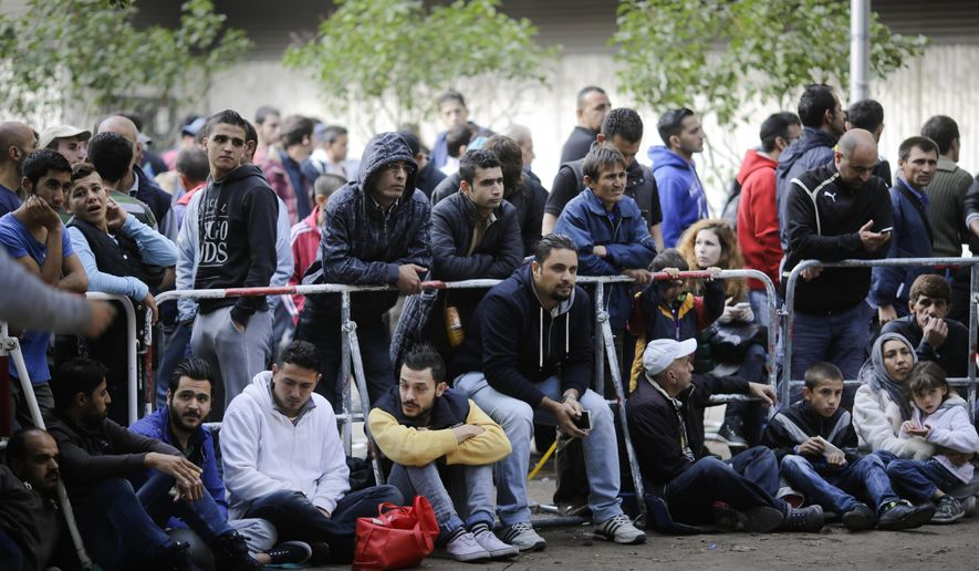Migrants gather in front of the reception center for refugees and asylum seekers as they wait for registration in Berlin, Friday, Sept. 4, 2015. (AP Photo/Markus Schreiber)