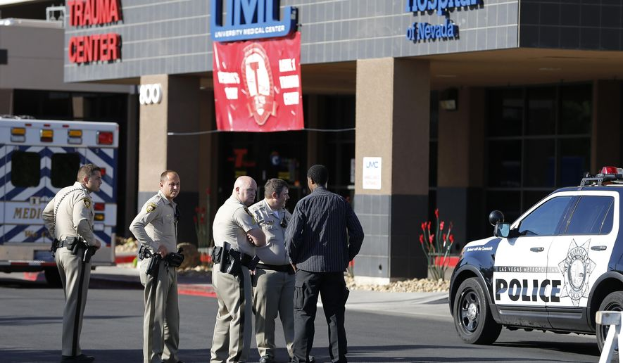 Las Vegas police officers stand in front of the University Medical Center Trauma Center where a fellow officer is in stable condition Friday, Sept. 4, 2015, in Las Vegas.  A police officer was wounded in the leg by a high-powered rifle and two men were arrested after a neighborhood search following a shootout in the backyard of a Las Vegas home. (AP Photo/John Locher)