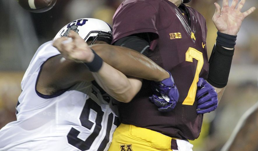 Minnesota quarterback Mitch Leidner (7) is stripped of the ball by TCU defensive end Terrell Lathan (90) during the first half of an NCAA college football game Thursday, Sept. 3, 2015, in Minneapolis. (AP Photo/Paul Battaglia)