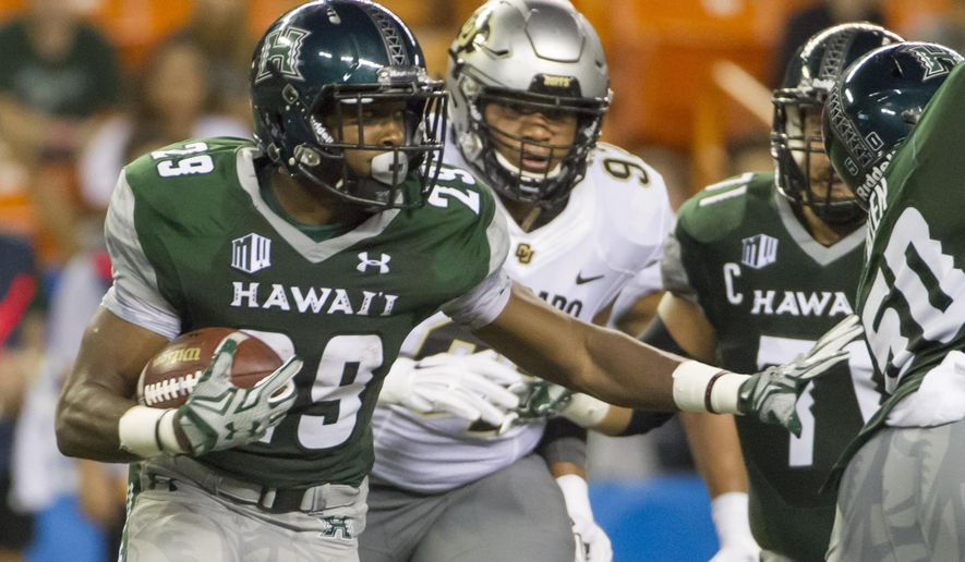 Hawaii running back Paul Harris (29) looks for an opening while being chased by Colorado defensive lineman Jordan Carrell, center, in the second quarter of an NCAA college football game, Thursday, Sept. 3, 2015, in Honolulu. (AP Photo/Eugene Tanner)