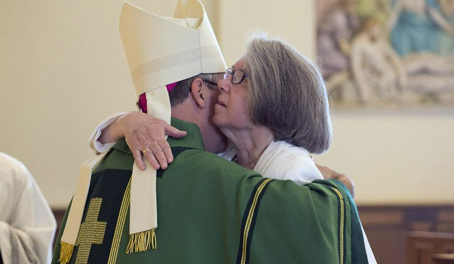 ADVANCE FOR WEEKEND EDITIONS SEPT. 5-6 - In this photo taken July 11, 2015, Sister Mary Ann Cody, right, hugs the bishop of The Diocese of Scranton, Pa., Bishop Joseph C. Bambera, during a service at Our Lady of the Eucharist Parish in Pittston, Pa., where she was installed as the first parish life coordinator in the diocese. In response to a dwindling number of Roman Catholic priests, diocese officials are relying on more men and women who aren't priests to oversee church ministries, including deacons, religious brothers and sisters and laypeople. (Christopher Dolan/ The Citizens' Voice via AP) MANDATORY CREDIT
