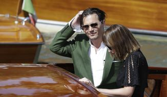 "Actors Johnny Depp and Dakota Johnson arrive for the press conference of the film ""Black Mass"" at the 72nd edition of the Venice Film Festival in Venice, Italy, Friday, Sept. 4, 2015. The 72nd edition of the festival runs until Sept. 12. (AP Photo/Andrew Medichini)"
