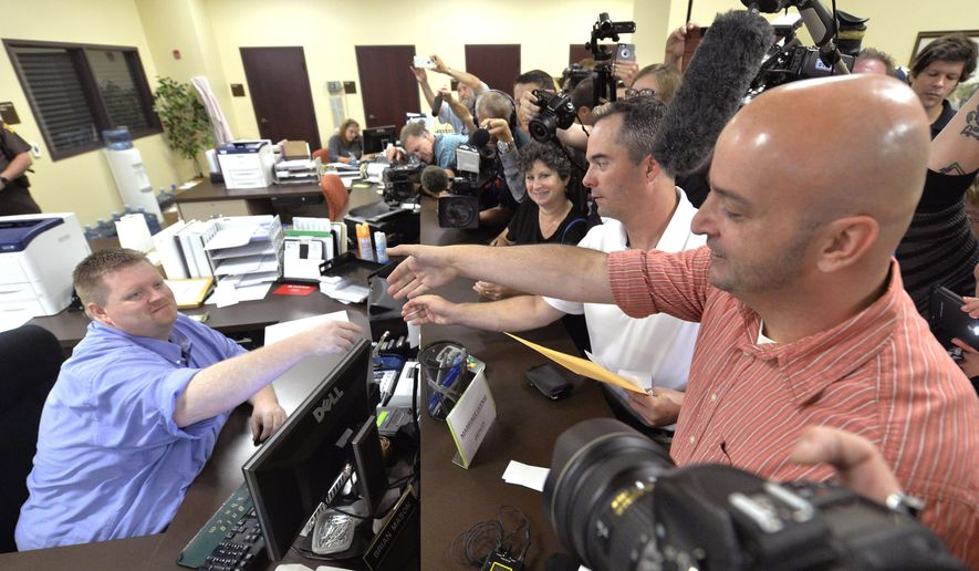 Rowan County deputy clerk Brian Mason, left, shakes hands with James Yates and his partner William Smith Jr. after issuing their their marriage license at the Rowan County Judicial Center in Morehead, Ky., Friday, Sept. 4, 2015. After four attempts, Yates and Smith were the first gay couple to receive their marriage license, hours after the county's defiant clerk was hauled to jail for refusing to license same-sex marriages. (AP Photo/Timothy D. Easley)