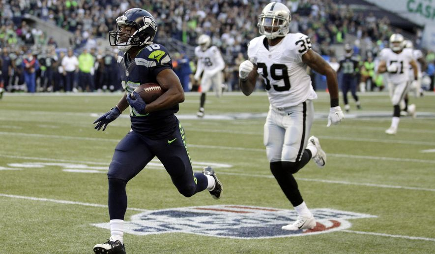 Seattle Seahawks wide receiver Tyler Lockett runs for a touchdown after catching a pass from quarterback Russell Wilson as Oakland Raiders cornerback Keith McGill (39) pursues, in the first half of a preseason NFL football game, Thursday, Sept. 3, 2015, in Seattle. (AP Photo/Stephen Brashear)