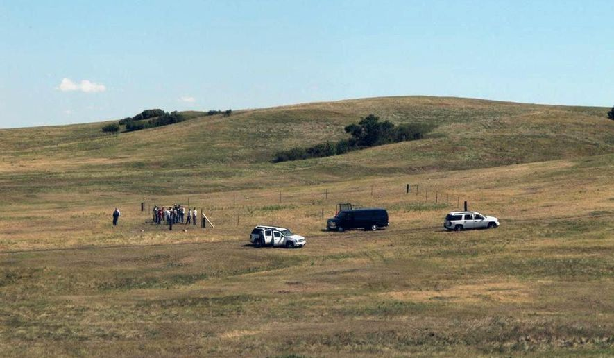 ADVANCE FOR USE SUNDAY, SEPT. 7 - In this photo taken Aug. 20, 2015, a small group looks at a prairie dog study area on the Mahto, S.D., Research Ranch deep into the Standing Rock Sioux Reservation grasslands. The ranch pasture is slowly being restored while a complex of researchers look into the sustainability of a small, grass-fed cattle operation that could be a trademark reservation product. (Lauren Donovan/The Bismarck Tribune via AP) MANDATORY CREDIT