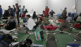 Migrants rest in an emergency shelter at the Hungarian-Austrian border in Nickelsdorf,  Austria, Saturday, Sept. 5, 2015, where they arrived in buses provided by Hungary's government from Budapest as Austria in the early-morning hours said it and Germany would let them in. (AP Photo/Petr David Josek)