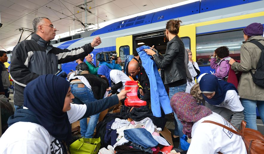 Refugees receive new clothes as they arrive at the Hauptbahnhof station in Salzburg, Austria, Saturday, Sept. 5, 2015 on their way from Hungary via Vienna to Germany. (AP Photo/ Kerstin Joensson)