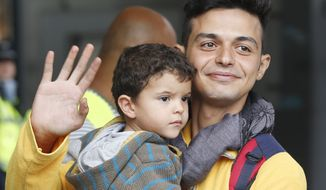 A father carries his child as they arrive at the main train station in Munich, Germany, Saturday, Sept. 5, 2015. Hundreds of refugees arrived in various trains to get first registration as asylum seekers in Germany. (AP Photo/Michael Probst)