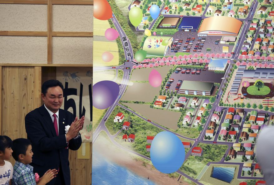 Mayor Yukiei Matsumoto, right, claps with children of Naraha residents during an event in Naraha, Fukushima, northern Japan, Saturday, Sept. 5, 2015. The Japanese town of Naraha on Saturday lifted a 2011 evacuation order that sent all its 7,400 residents away after the nearby Fukushima nuclear plant was crippled by a tsunami and spread contamination. Naraha was the first among seven municipalities forced to empty entirely due to radiation contamination following the massive earthquake and tsunami that sent the reactors into meltdown. (AP Photo/Koji Sasahara)