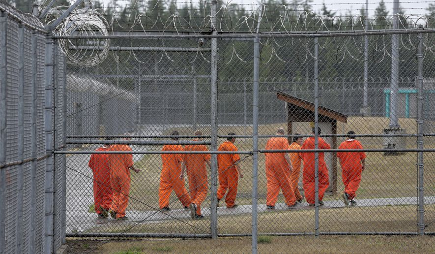 In this Aug. 31, 2015 photo, prisoners walk toward an exercise yard at the Washington Corrections Center, in Shelton, Wash. For dozens of maximum custody prisoners at the facility who do not get to spend time outside, 23 hours each day is spent alone in a small cell with one hour to walk or run, also alone, in a recreation room with high concrete walls and a metal-grated roof. In the coming weeks, some prisoners in solitary confinement  will have the option of using their hour outside of their cells to watch sunsets, mountains and underwater seascapes on video, with the hope that inmates will be calmer, and guards will have to deal with fewer outbursts or violent interactions. (AP Photo/Ted S. Warren)