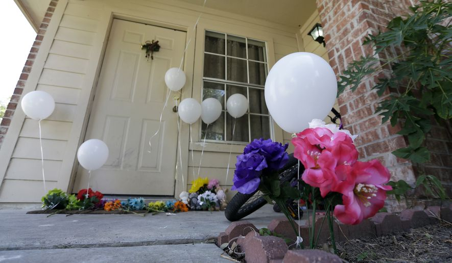 Flowers and eight balloons are seen at a house where eight people were killed on Aug. 8 in Houston. A family of six children and two parents were handcuffed and fatally shot in the head at a Houston home by a man with a violent criminal history who had previously been in a relationship with the mother and had a dispute with her, authorities said. David Conley, 48, was charged with capital murder in the deaths. (Associated Press)
