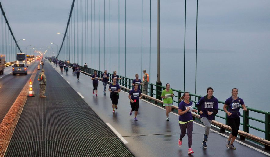 Runners lead the way across the Mackinac Bridge, Monday, Sept. 7, 2015, during the 58th annual Mackinac Bridge Walk, in Mackinaw City, Mich. Selected runners are allowed to precede the governor and 40,000 walkers who followed them across the span between Michigan's upper and lower peninsulas. (AP Photo/John L. Russell)