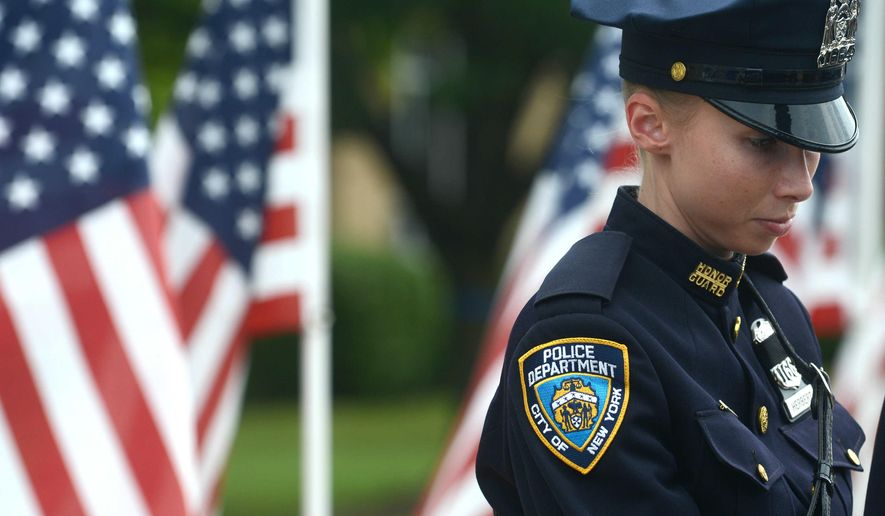 New York Police Department officer Lauren Herbert pauses after arriving  for funeral services for Fox Lake police Lt. Charles Joseph Gliniewicz at Antioch High School in Antioch, Ill., Monday, Sept. 7, 2015. Hundreds of law enforcement officers are attending the funeral of  the suburban Chicago police officer who was fatally shot last week. (Patrick Kunzer/ Daily Herald via AP) MANDATORY CREDIT, MAGS OUT