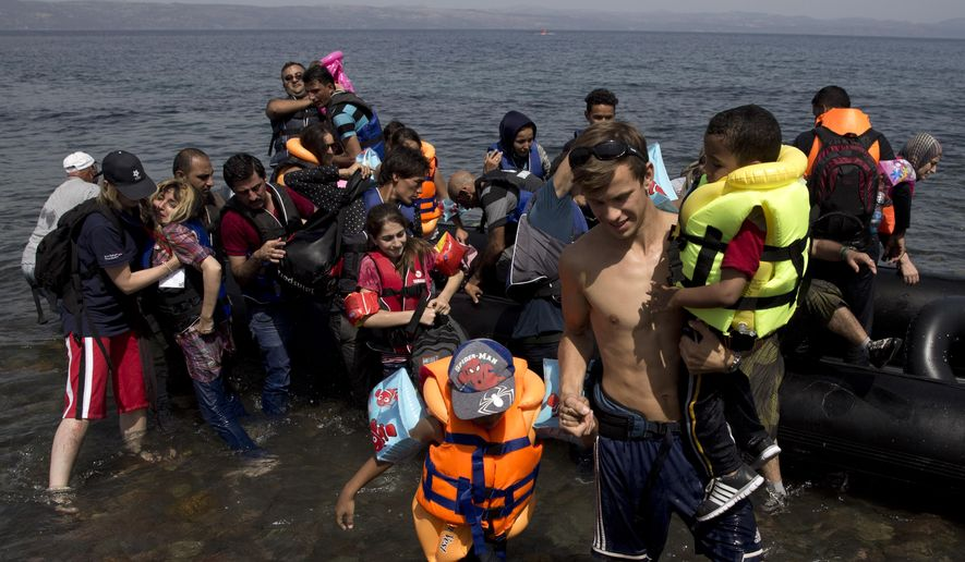 A volunteer helps two Syrian children as they arrive aboard a dinghy after crossing from Turkey, on the island of Lesbos, Greece, Monday, Sept. 7, 2015. The island of some 100,000 residents has been transformed by the sudden new population of some 20,000 refugees and migrants, mostly from Syria, Iraq and Afghanistan. (AP Photo/Petros Giannakouris)