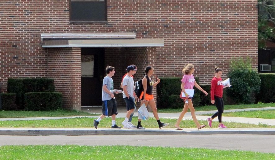 In this Aug. 29, 2015, file photo, students walk past the public safety building at St. Bonaventure University in St. Bonaventure, N.Y. Students at New York state's private colleges and universities return to campus with a new, affirmative sexual consent policy to combat campus sexual violence. (AP Photo/Carolyn Thompson)